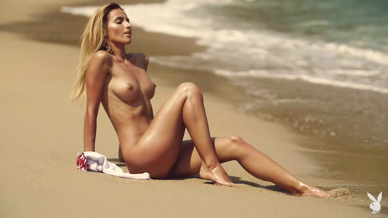 Striptease at the beach with a beauty playing in the sand